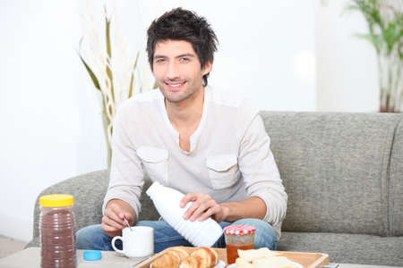 spoor: Man having breakfast on sofa