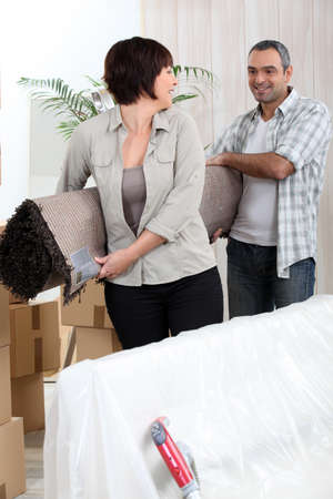 Couple carrying rolled-up carpet photo