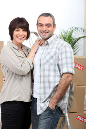 a couple behind  a pile of cartons inside a house photo