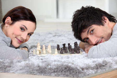 Couple playing chess in bed photo