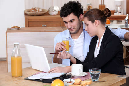 Woman going over a work presentation with her boyfriend during breakfast photo
