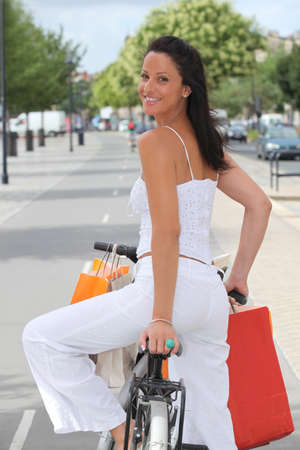 Back shot of a young woman clothes shopping on a bicycle photo