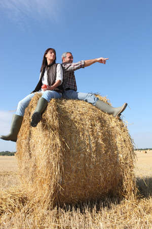 Farmer and wife sat on hay roll