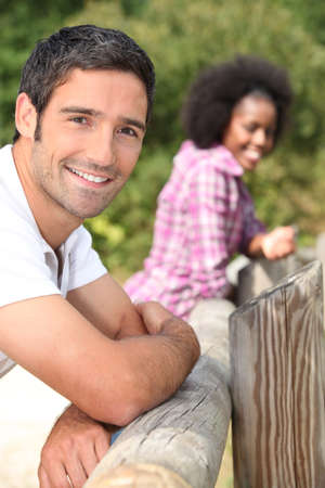 leaning by barrier: couple leaning against a wooden barrier