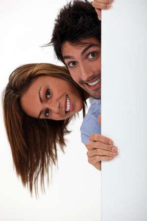abriendo puerta: joven mujer y hombre que se esconde detrás de la puerta