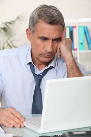 loosen: mature man working home with laptop Stock Photo