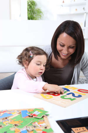 Mother and young daughter doing jigsaw puzzles photo