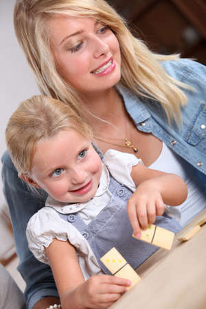 nanny: Young woman and little girl playing with dominoes