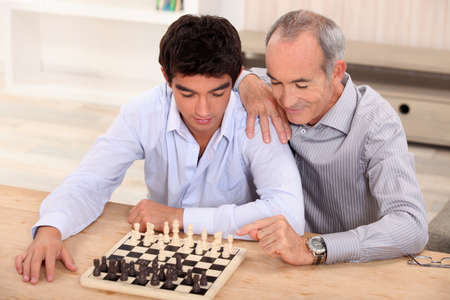 Father and son playing chess photo