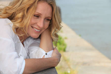 leaning by barrier: Smiling woman on a boardwalk