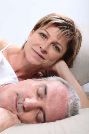 Woman lying next to her sleeping husband photo