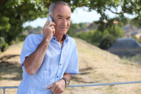 Grey-haired man making telephone call in park photo