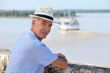 60 64 years: Man in a straw hat watching a ferry cross the Gironde estuary