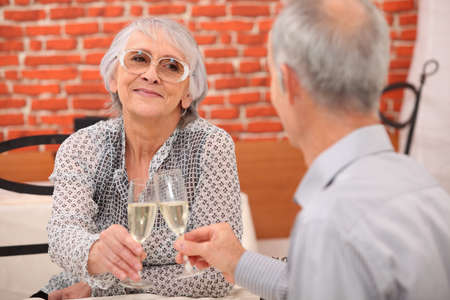 65 years old: older couple toasting at restaurant