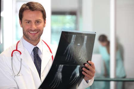 pacientes: Médico feliz mirando a imagen de rayos X de la mano