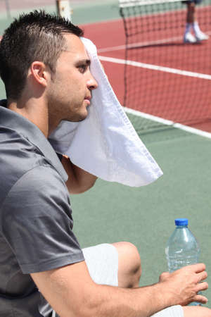tennis player sweeping out the sweat from his forehead photo