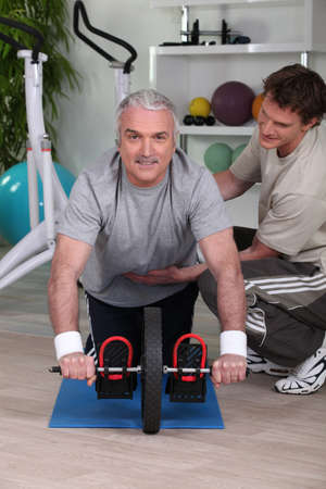 Middle-aged man working with personal trainer Stock Photo - 11399103