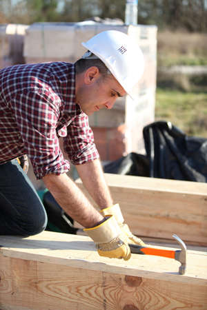 Man working on large wooden structure photo