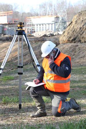 ingeniero civil: Un agrimensor escribiendo en su port�til mientras habla por tel�fono