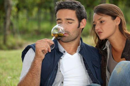 degustating: Couple tasting wine in field