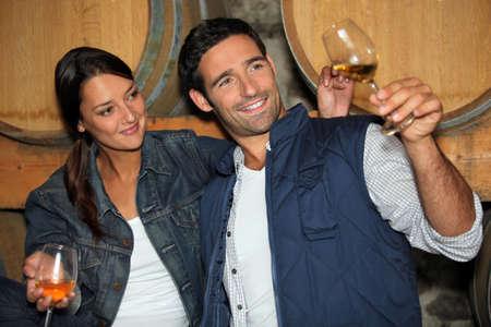 weinverkostung: L�chelnd Mann und Frau Weinprobe in einem Keller Lizenzfreie Bilder