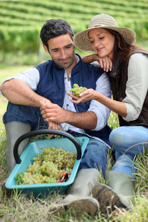 Couple in field eating grapes photo