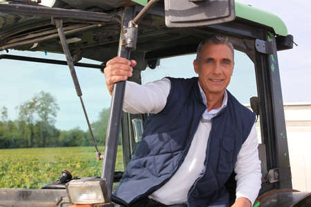Farmer in the cab of his tractor photo