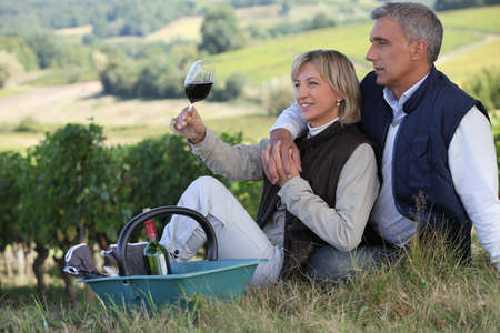 Man and woman tasting wine in a vineyard photo