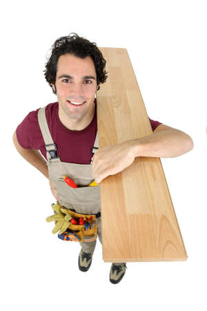 woodworker: Happy woodworker carrying plank standing isolated on white background