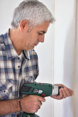 grey haired: Grey- haired man drilling hole in wall Stock Photo