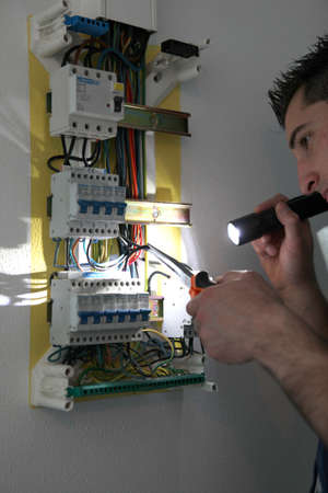 electric circuit: Tradesman fixing a circuit breaker