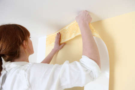 Woman putting up a wallpaper border photo
