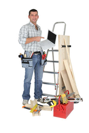 stood: Carpenter stood by ladder with laptop