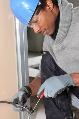 Afro-American laborer installing wiring photo