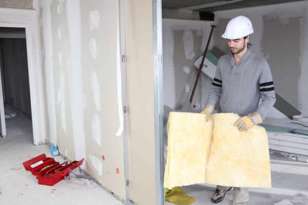 gypsum: Tradesman installing insulation