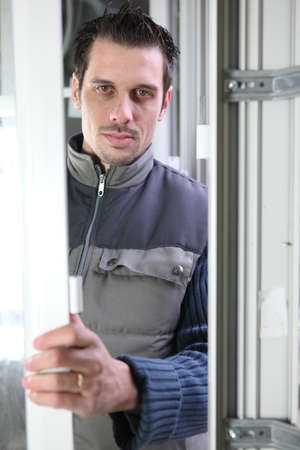 straight faced: Worker installing a door Stock Photo