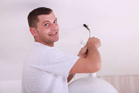 t bulb: Man at home fixing ceiling light