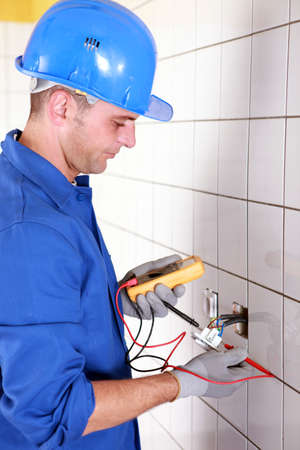 voltmeter: Plumber checking wiring with a voltmeter Stock Photo
