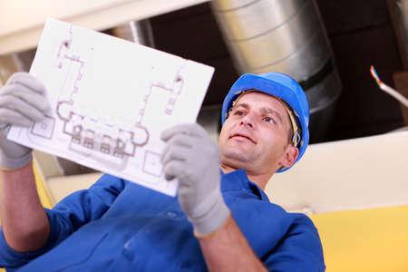 techniek: Man kijkt naar de plannen voor een verwarmingsinstallatie