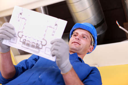 ducts: Man looking at plans for a heating installation