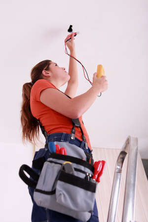 descarga electrica: Mujer medir un alambre Foto de archivo