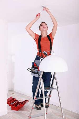 portrait of a young woman doing electricity work photo