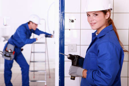 Female electrician with a power drill photo