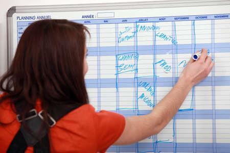 woman back view: Girl writing on calendar