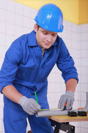 jumpsuite: young technician cutting a pipe Stock Photo