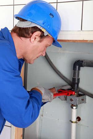 lekken: Man installatie van waterleidingen met een grote sleutel Stockfoto