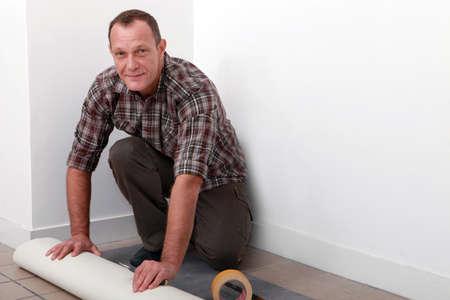 floor covering: Man putting down linoleum flooring