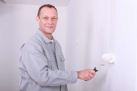 Man in overalls painting a room white photo