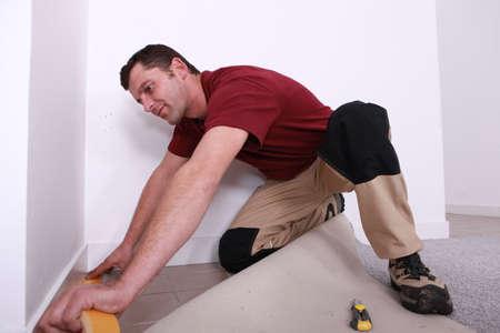 handyman laying wall-to-wall carpet photo