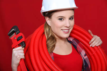 Female construction worker holding corrugated tubing and a pipe wrench photo